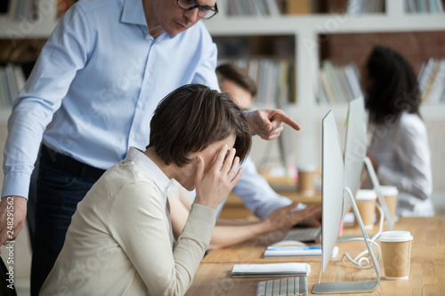 Photo  Stressed female employee suffering from discrimination of angry male boss