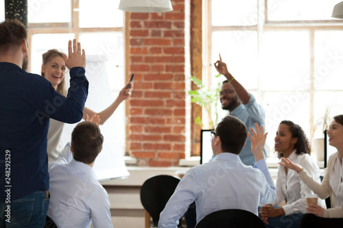 Business people raising hands voting asking questions at corporate training Wallpaper Mural