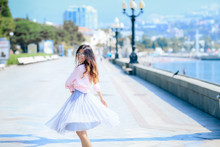 Girl Walking Along The Seafront In Dress In Hot Summer Day