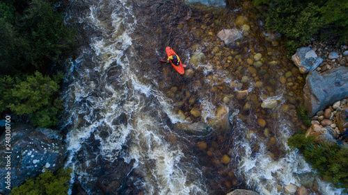 Valokuva  Aerial image of a white water kayaker on a mountain river in flood after good wi