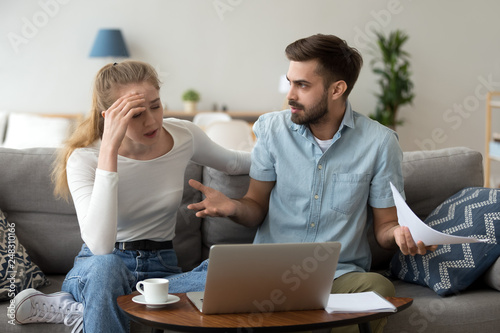 Stressed unhappy couple arguing about expenses with laptop and papers Wallpaper Mural