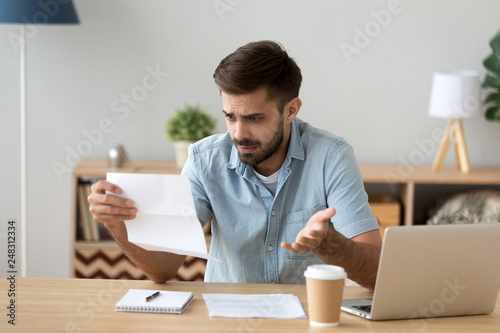 Fotografía  Confused frustrated man holding mail letter reading shocking unexpected news
