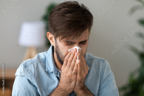 Obraz Sick man got flu allergy sneezing in handkerchief blowing nose - fototapety do salonu