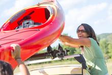 Middle Age Woman Lifting Kayak Onto Car Roof Rack