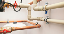 Different Copper And Plastic Pipes And Other Valves In The Boiler Room