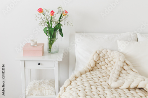 Fotografie, Obraz  Cozy bedroom interior: white wall, bed with white linen, light beige thick yarn knitted woolen merino chunky blanket or plaid, pillows, bedside table, vase with tulips flowers