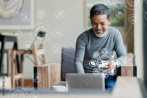 Valokuvatapetti Asian or Hispanic man using Laptop and credit card payment shopping online with icon customer network connection on screen and connecting with omni channel system
