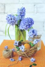 Orange Easter Egg In Nest And Blue Flowers.