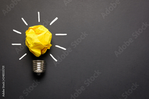 Photo  Great idea concept with crumpled yellow paper light bulb isolated on dark backgr