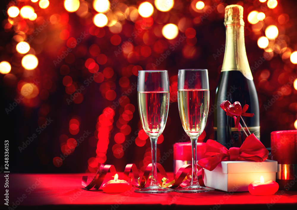 Fototapeta Valentine's Day romantic dinner. Champagne, candles and gift box over holiday red background. Wedding celebrating. Birthday party