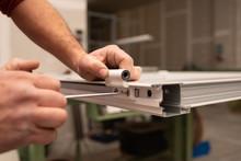 Close Up Of Worker Hands Assembling A Hinge On Aluminium Door