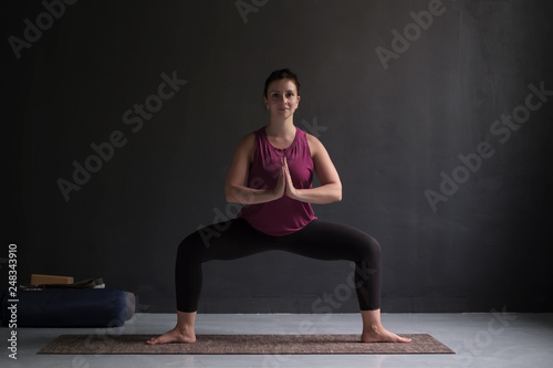 Fotografie, Obraz  Beautiful young yoga model working out indoor doing Goddess or Sumo Squat Pose