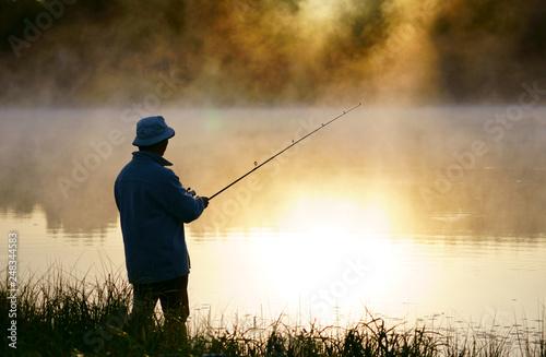 Fotobehang Vissen Caucasian fisherman, 50's, at the lake with fog, early morning just before sunrise.