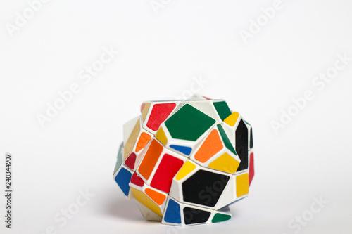Photo  Multi-colored unusual puzzle, strange shape rubik's cube, on a white background