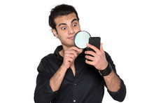 A Man In A Black Shirt Looks Through A Magnifying Glass At A Mobile Phone