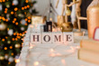 Christmas. Christmas tree decorated with a garland. Gold and white Christmas balls. Christmas photo zone. Burning light bulbs on the garland. Figurine in the form of a snowman. Cubes labeled home.