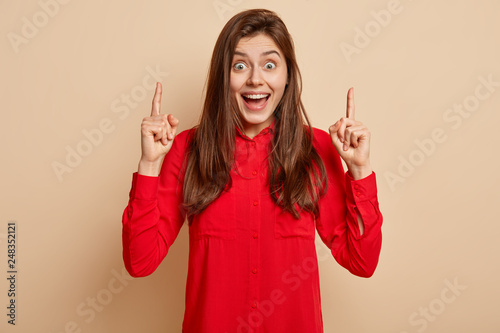Foto  Overjoyed brunette European woman points up with satisfied and delighted express