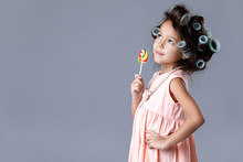 Funny Little Child Girl In Pink Dress And Hair Curlers Holding Lollipop On Gray Background.