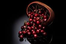 Fresh Cherry In A Wicker Basket On A Black Background.