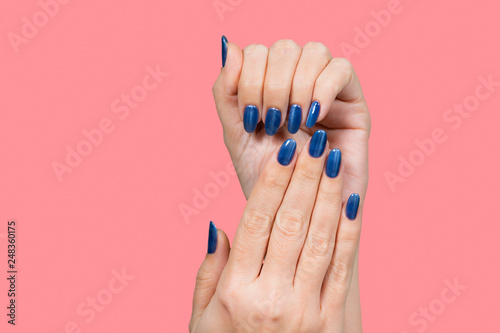 Fényképezés  Closeup view of beautiful female hands with blue glossy professional manicure isolated on pink background