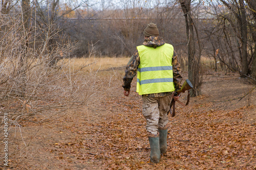 Foto op Canvas Jacht Silhouette of a hunter with a gun in the reeds against the sun, an ambush for ducks with dogs