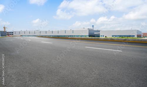 Fotografiet  Road asphalt pavement and modern factory warehouse..