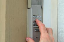 Hand Entering Code On Keypad - Garage Door Opener - Home Security