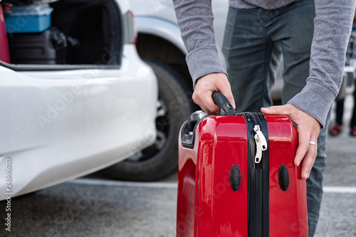 Foto  Young traveler loading and picking up red suitcase into truck of car