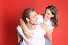 Image Of Caucasian Couple Looking At Each Other And Smilling While Sitting On Back Of Content Man Isolated Over Red Background.