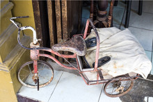 Old Rusty Tricycle For Children On A City Street