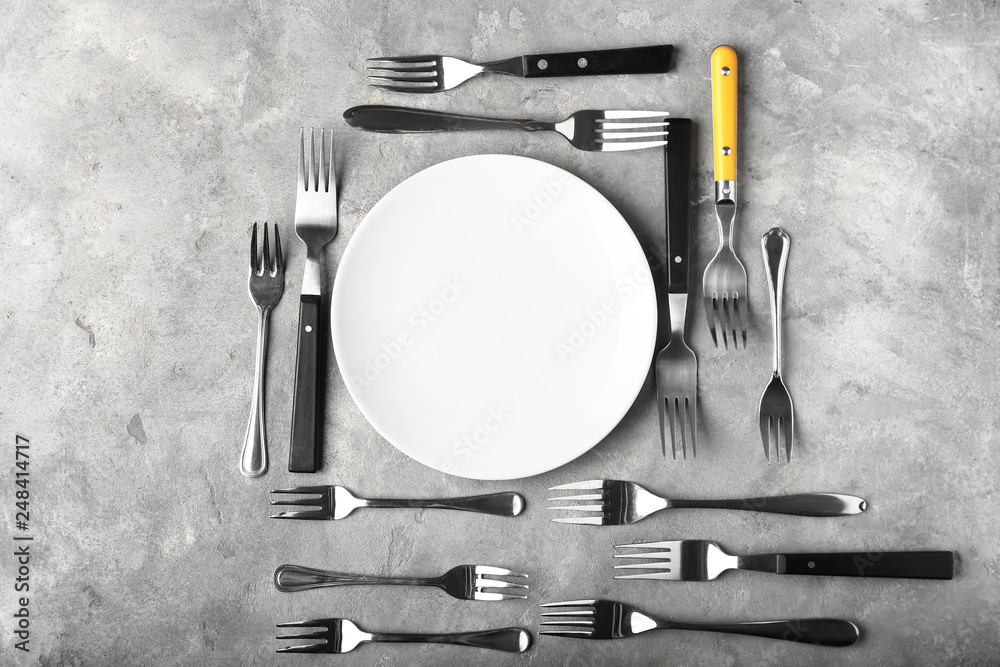 Fototapeta Table setting with a lot of forks on grey background