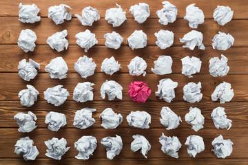 Pojęcie kreatywności i inspiracji przedstawione przez wiele białych papierowych kulek i jeden kolor