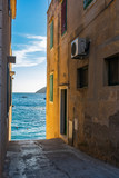 Fototapeta Uliczki - A narrow traditional dalmatian street exiting on the beach, view of blue Adriatic sea and an island in the background. Summer scene from Komiza town, Vis island in Croatia, Europe