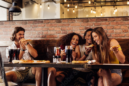 Group of friends having pizza at restaurant