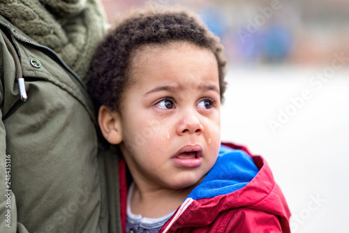 Fotografie, Obraz  Portrait of a little upset toddler boy crying, scared boy in the arms of his mot