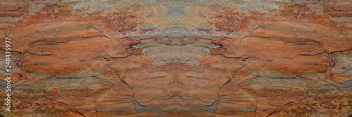 Rust stone wall in panorama view or grunge stone texture