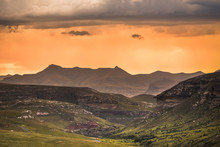 A Dramatic Scene Of Golden Sunset And Storm Clouds Over The Drakensberg Mountains Surrounding The Amphitheatre, Seen From Golden Gate Highlands National Park In The Drakensberg, South Africa