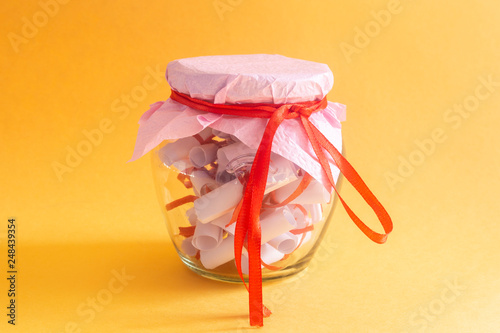 Photographie  Desires, Wishes or Dreams written on rolled papers in glass jar on yellow