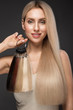 Leinwanddruck Bild - Beautiful blond girl with a perfectly smooth hair, classic make-up with a palette for hair extensions in the hands. Beauty face.