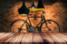 Wood Table Top On Blur Background Of Coffee Shop (or Restaurant) Interior And Bicycle On The Wall - Can Be Used For Display Or Montage Your Products