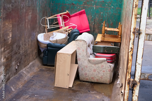 Photo Old furniture and chairs rubbish in steel container for charity jumble sale at r