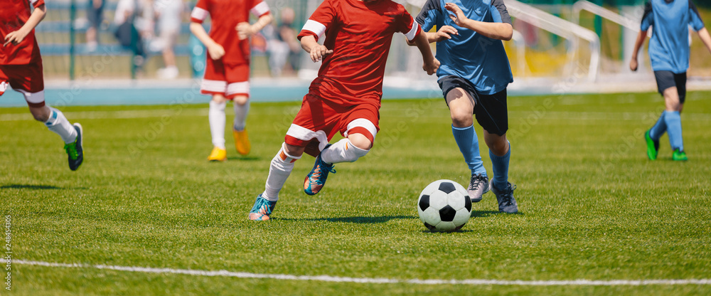 Fototapeta Football Soccer Players Running with Ball. Footballers Kicking Football Match. Young Soccer Players Running After the Ball. Kids in Soccer Red and Blue Uniforms. Soccer Stadium in the Background
