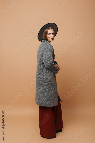 Fotografía  Young beautiful pensive woman with hat in gray coat and wide pants thoughtfully