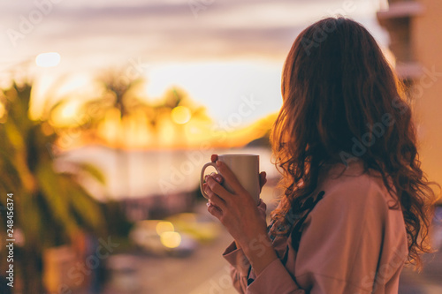Lonely romantic girl drinking coffee looking at sunset. Fototapete