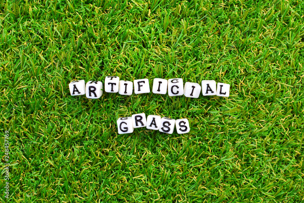 Artificial grass background and little cubes with thematic text