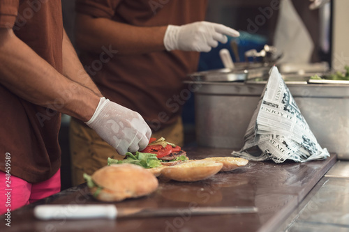 Fototapety, obrazy: fast food burger with tomatoes and pickels inside the food truck van, street food cuisine at the food street market festival for foodies
