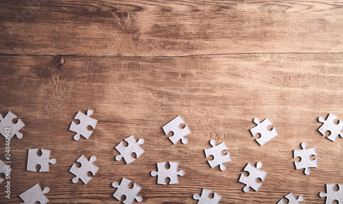 Photo  Pieces of the jigsaw puzzles on wooden background.