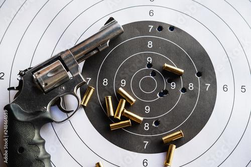 Fototapeta Pistol revolver with bullets and target