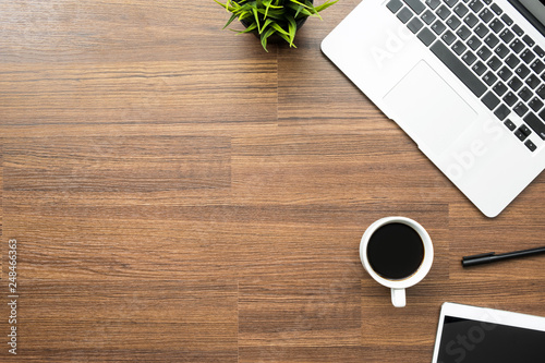 Fotomural  Wood office desk table with laptop, a cup of coffee and supplies