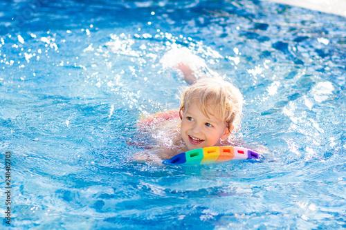 Fototapeta Child learning to swim. Kids in swimming pool. obraz